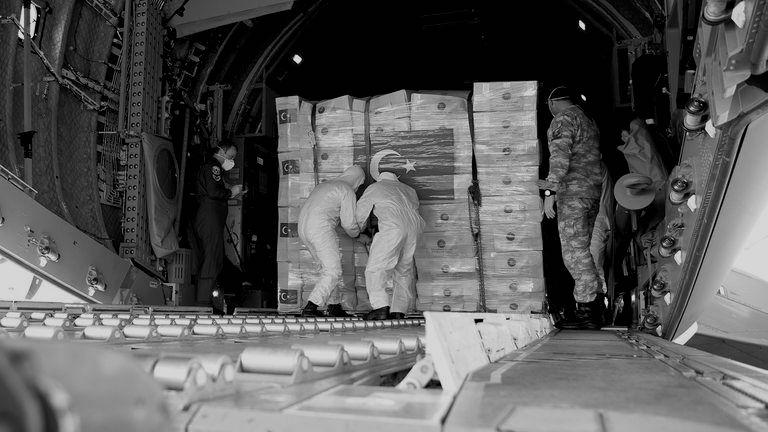 Soldiers loading PPE into the back of an aeroplane